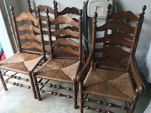 6 beautiful wooden and wicker chairs, with one captains chair