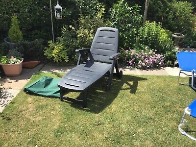 Green plastic sun lounger With wheels and arm rests