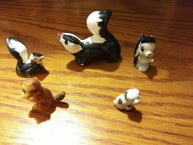 3 Skunk Figurines-1 resin like raccoon and 1 small dog