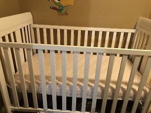 Two white cribs and two crib mattresses