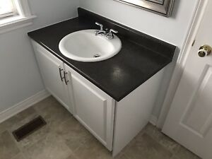 Bathroom Vanity with Dark Countertop, Sink, and Taps