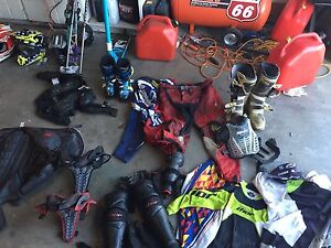 LOTS OF DIRT BIKING GEAR AND PRO SKIS AND POLLS WOTH BOOTS