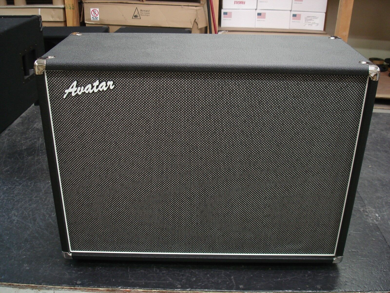 The cabinet is wrapped in black tolex covering with the Black and Silver  weave grill cloth with white piping