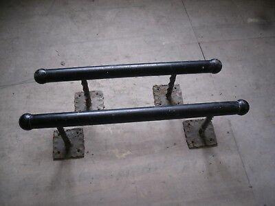 A pair of small black cast iron bar foot rests/door handles