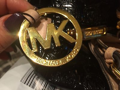 This is a genuine MK zipper pull.  It's even, smooth and a beautiful gold (not brassy yellow colour).