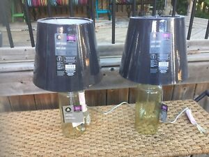Two small amber glass table lamps with black shades