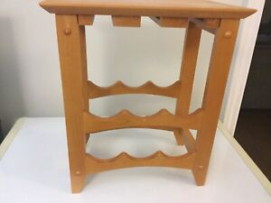 Wooden table holds wine bottle and wine glasses