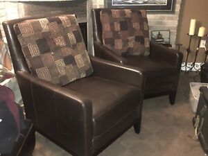 two brown leather chairs w/ pillows