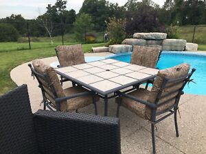 Patio Table and chairs with cushions and a lounge chair.