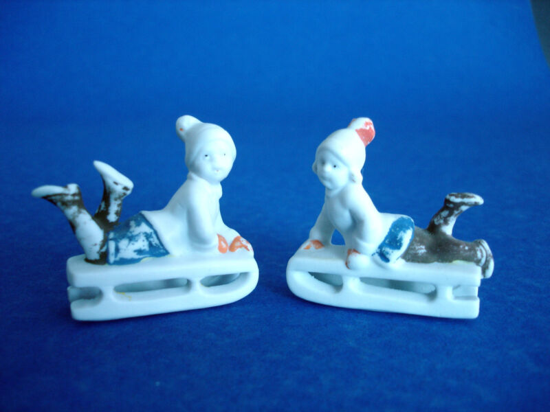 PAIR ANTIQUE GERMAN BISQUE MINIATURE CHRISTMAS FIGURINES - BOY & GIRL ON SLEDS