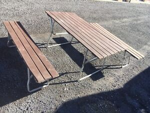 Wooden picnic table with bench's folds flat