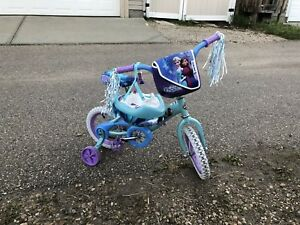 Girls bike with training wheels and helmet.