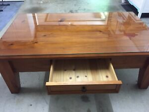 Solid stained timber coffee table with a glass top and hidden draw.