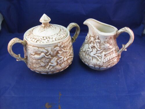 POTTERY CREAM PITCHER AND SUGAR BOWL W EMBOSSED SCENIC DESIGN