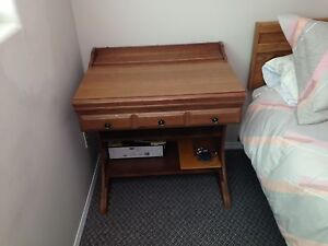 Desk dresser and bed with sheets blanket and cover