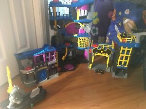 Bat cave and Gotham city set and two remote controlled trucks.