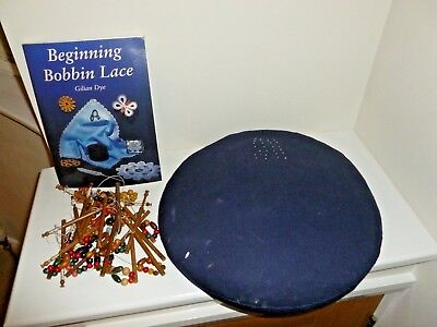 Round bobbin lace pillow, with plastic bobbins and beginning bobbin lace book