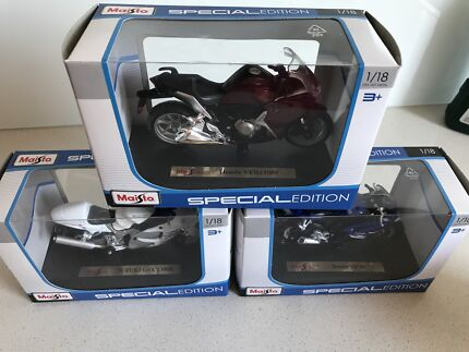 Die cast motorbikes each boxed and on stands.