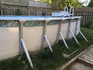 Large Above ground pool with pump and cleaning supplies.