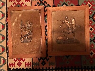 Two wooden panels with animal skin and decorative copper African figures. ()
