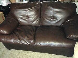 Dark brown faux leather love seat.