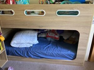 A white timber double bunk with a mattress