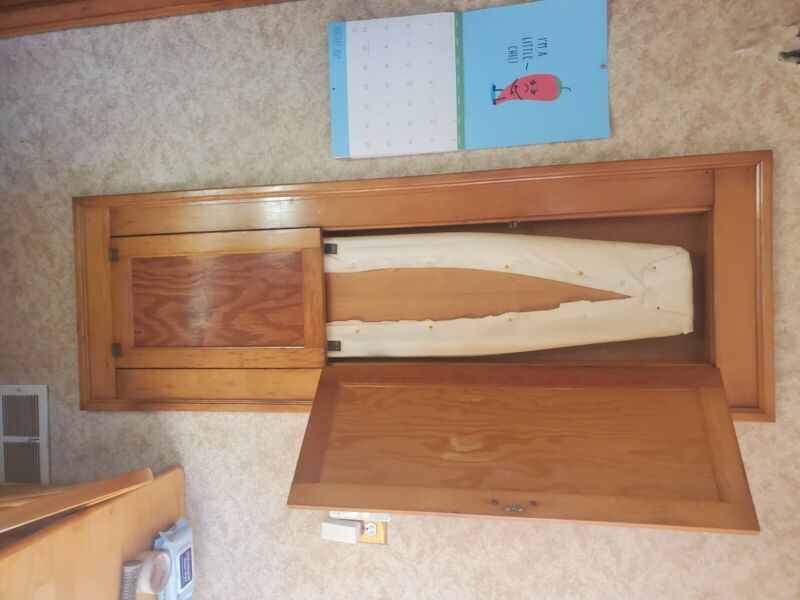 In wall mounted ironing board with arm sleeve. Antique built into wall.
