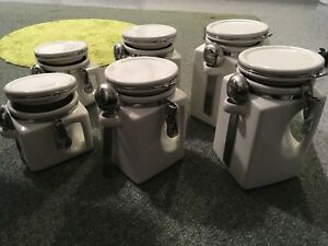6 pc white canister set with attached spoons.