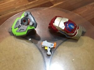 Three Nerf toy guns and iron man gauntlet disc shooters