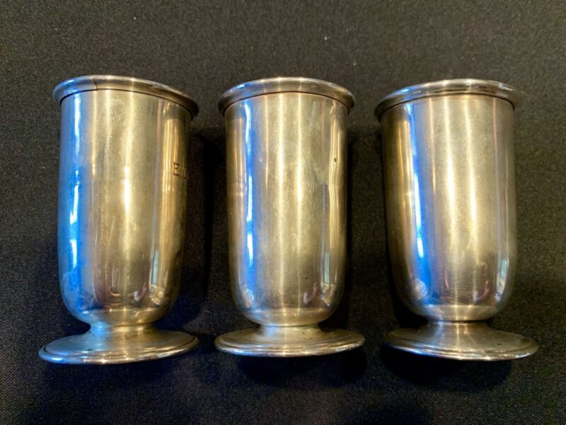 THREE ANTIQUE STERLING SILVER SHOT CUPS.