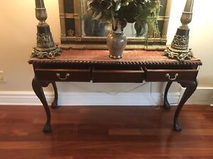 An antique mahogany solid wood console with 3 drawers