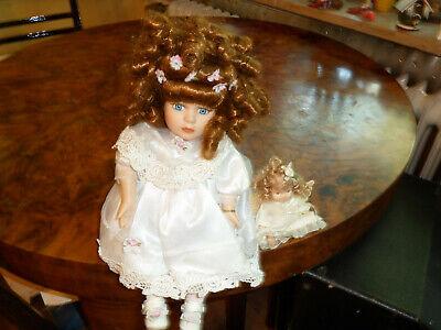 Porzellanpuppe sitzend Spieluhr braune Locken weißes Kleid und kleine puppe