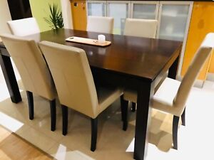 Brown dining table set with six leather chairs