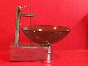 Glass vessel sink with chrome wall mount.