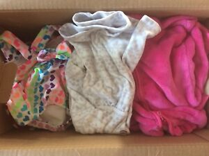Assorted baby girl bathing suits, sweaters and bibs