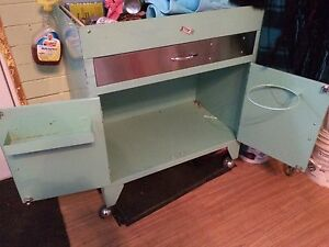 Two vintage mint green medical tables on wheels