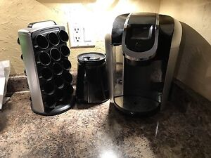 Black Keurig coffee maker and cup carousel and thermos