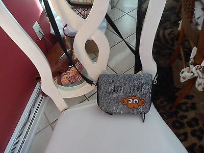 Small black and gray cross body handbag with a monkey on front ()
