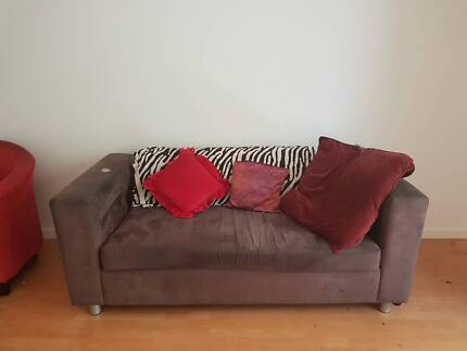 Brown velour couch and 2 red bucket armchairs