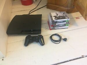 PS3 slim with controller, controller charging cable and games