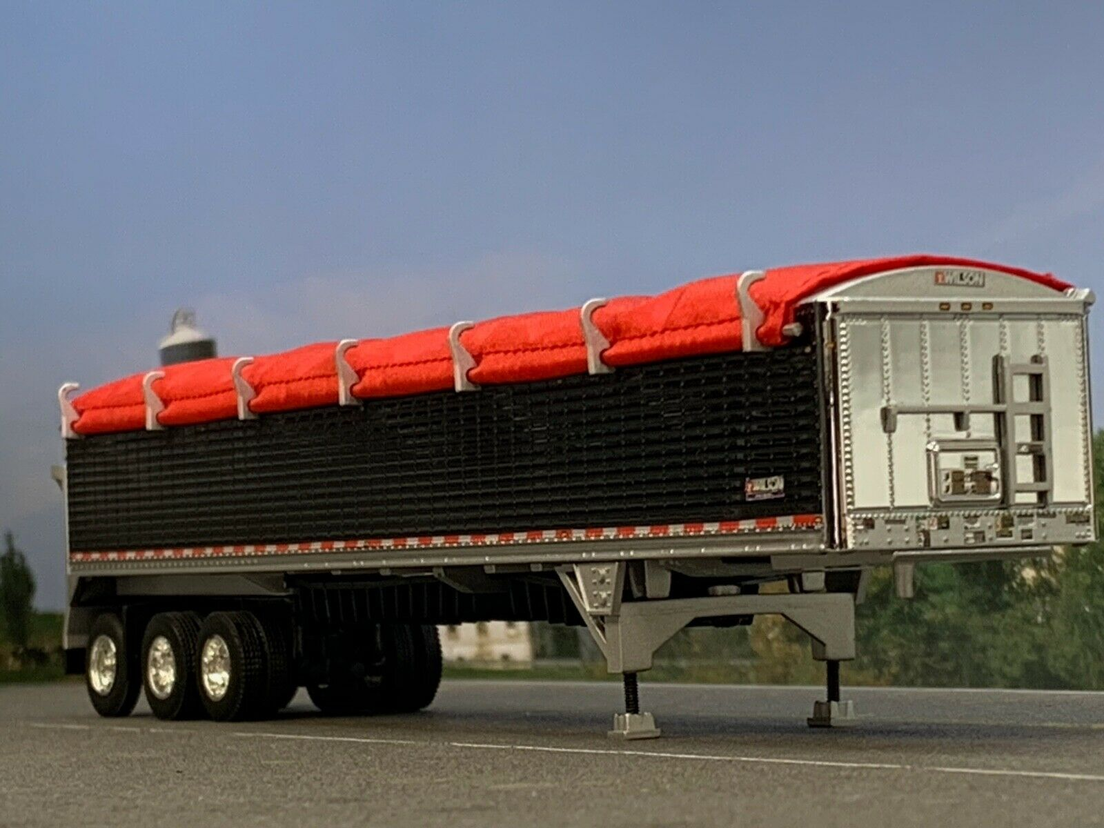 1/64 DCP BLACK WILSON PATRIOT TRI-AXLE (DUALS) BELT TRAILER W/ RED TARP