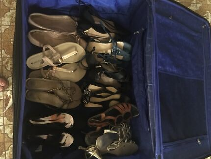 Suitcase filled with ladies shoes and handbags