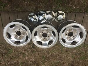 Three Ford F-150 aluminum rims with center caps