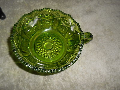 GREEN GLASS HANDLED DISH WITH STAR PATTERN