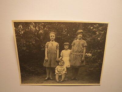 4 Kinder - Mädchen im Kleid und Kleinkind in einem Garten / Foto ()