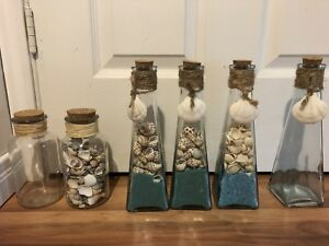 Glass bottles with shells and sand