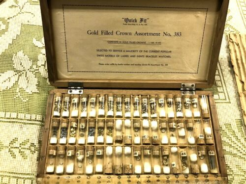 VINTAGE WATCHMAKERS LARGE CABINET OF GOLD FILLED CROWNS,WHITE AND YELLOW.NOS