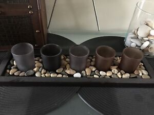 Candle holders on wooden rock tray