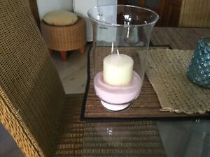 Large clear glass candle holder with cream candle and pink sand
