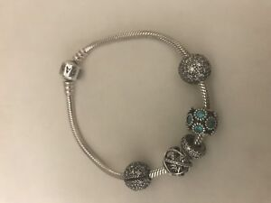 Pandora Bracelet with two clips, 2 charms and 1 spacer.